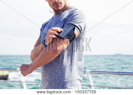 Male runner listening to music adjusting settings on armband for smartphone outdoors