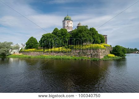Old Vyborg Castle among trees and water at summer day in Russia