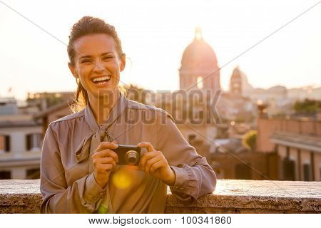Laughing Elegant Woman Looks Up From Checking Photos In Rome
