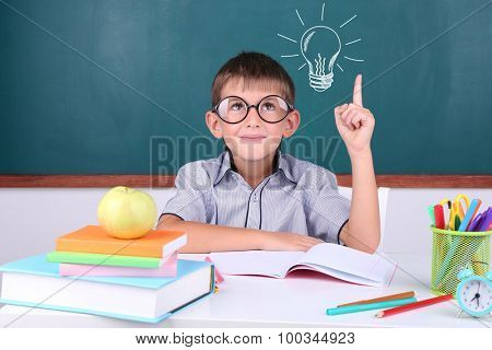 Schoolboy near blackboard with idea bulb above the head