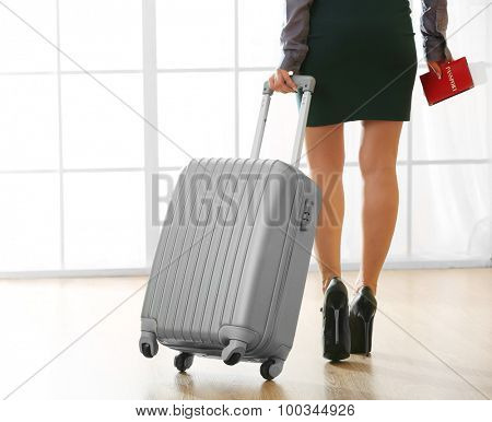 Woman with suitcase in hall