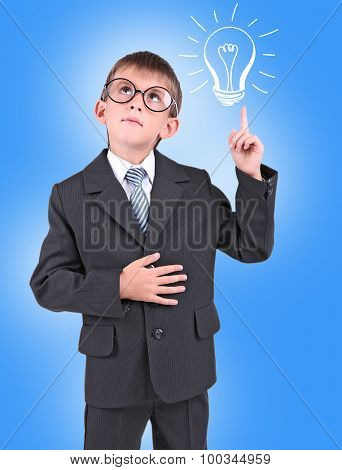 Little schoolboy with idea bulb above the head on blue background