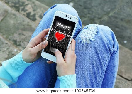 Woman with mobile phone with health book app on the screen, outdoors