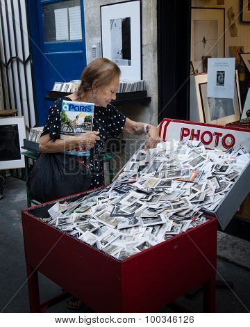Senior woman looking at old photos at an outdoor market in paris