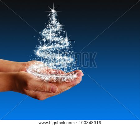 Hands holding a delicate glowing magic Christmas tree of stars