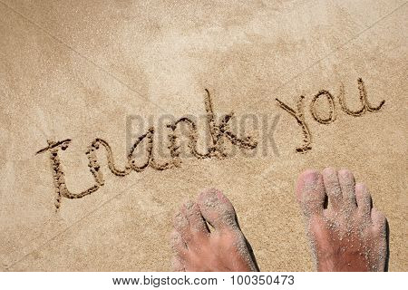 Concept or conceptual thank you text handwritten in sand on a beach in an exotic island background with feet