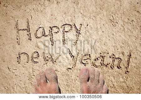 Concept or conceptual hand made or handwritten Happy new year text in sand on a beach in an exotic island with feet