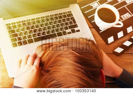 Head of tired scriptwriter on laptop at wooden desk background