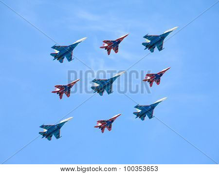 Aerobatic groups Russian Knights and Swifts on MIG-29 and SU-27 fighters in flight against blue sky