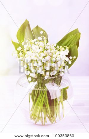 Beautiful lilies of the valley in glass vase on wooden table