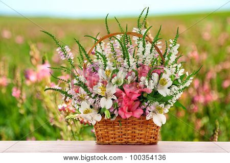 Beautiful wildflowers in wicker basket on field background