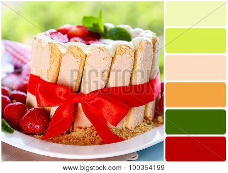 Tasty cake Charlotte with fresh strawberries on green nature background and palette of colors