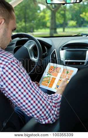 Man sitting in the car and holding tablet with map gps navigation application