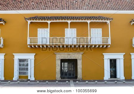 Frontal View Of Yellow House With White Doors, Window And Balcony