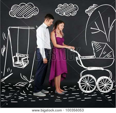 Young couple with baby carriage, on black background