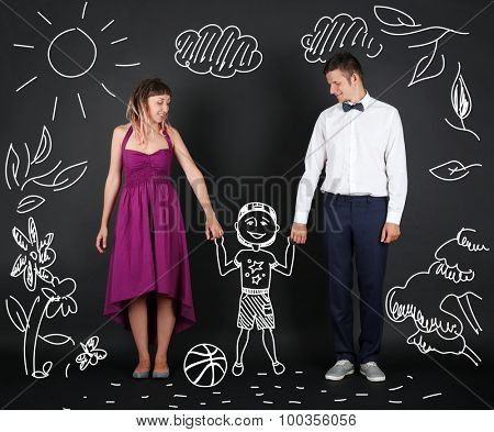 Funny young couple with child, on black background