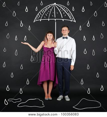 Funny young couple with umbrella, on black background