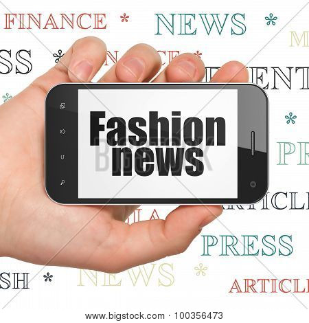 News concept: Hand Holding Smartphone with Fashion News on display