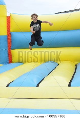 A young boy playing on a bouncy castle