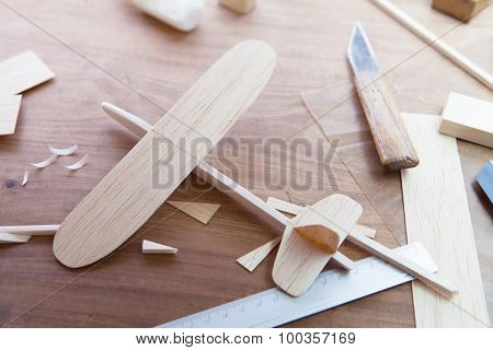 Making model airplane from wood. Wooden air plane handcrafted with balsa wood, on work table by the window. Airplane, knife, balsa wood material and glue on table. Shallow depth of field.