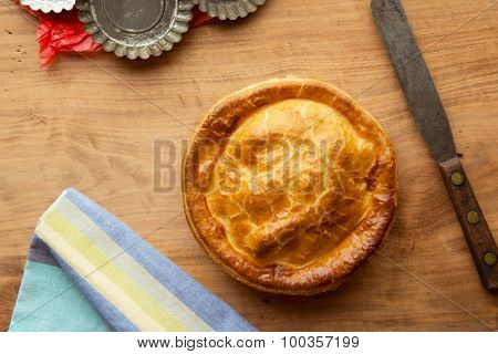 Baked pie on old kitchen table with well used baking molds and spatula.