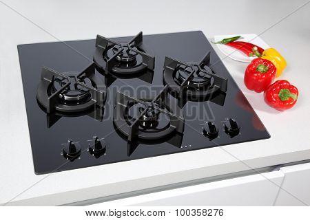 Black glass gas hob in modern kitchen.