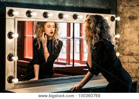 Beautiful fashion blond woman posing near the mirror