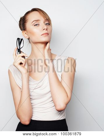 Business, finance and people concept: young business woman with glasses. Over grey background.