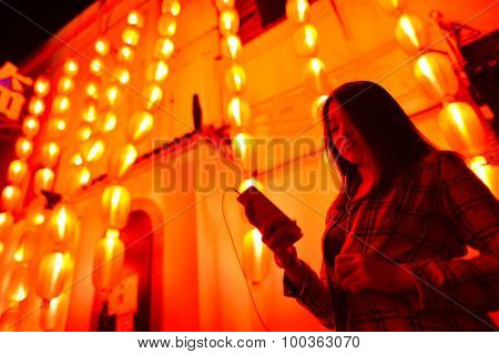Chinese teenager with cell phone near chinese new year lanterns