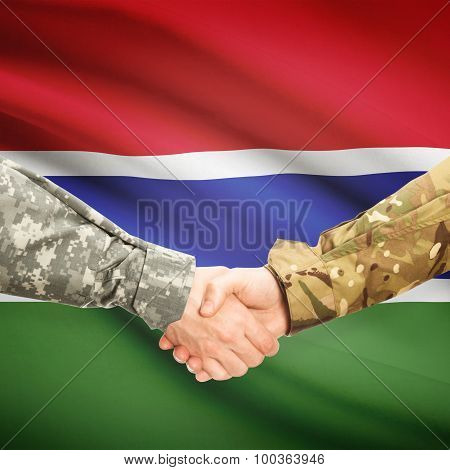 Men In Uniform Shaking Hands With Flag On Background - Gambia