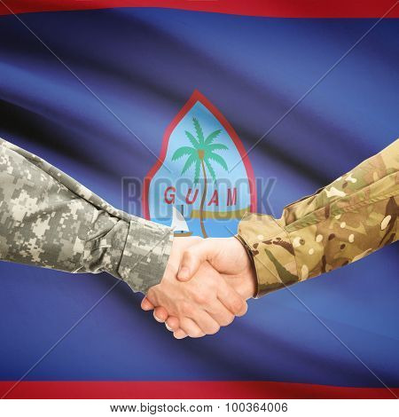 Men In Uniform Shaking Hands With Flag On Background - Guam