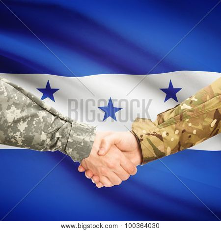 Men In Uniform Shaking Hands With Flag On Background - Honduras