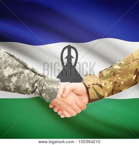 Men In Uniform Shaking Hands With Flag On Background - Lesotho