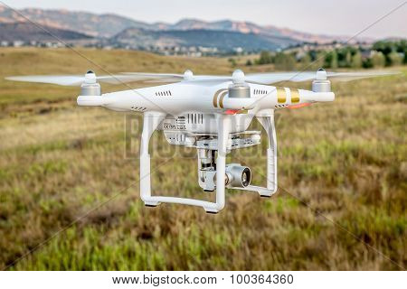 FORT COLLINS, CO, USA, SEPTEMBER 1, 2015:  Radio controlled Phantom 3 quadcopter drone is flying with a camera over foothills of Rocky Mountains.