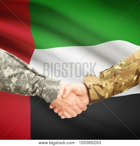 Men In Uniform Shaking Hands With Flag On Background - United Arab Emirates