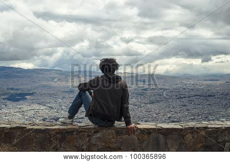 Anonymous Man With Black Curly Hair In Brown Jacket Sitting On Stone Wall And Looking Over Bogota