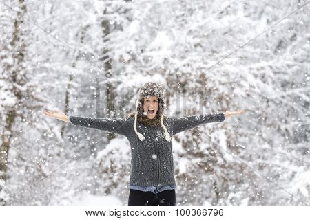 Excited Young Woman Playing In Snowy Woods