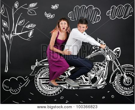 Funny young couple ride the motorcycle, on black background