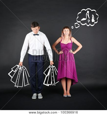 Funny young couple with shopping bags, on black background