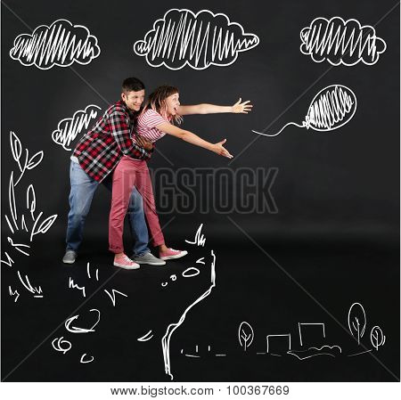 Funny young couple catching balloon on black background