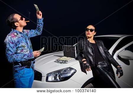 Two gangsters with dollars near the car