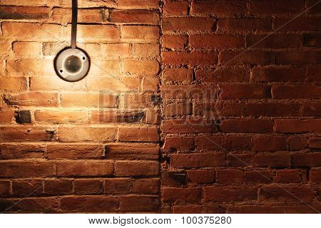 Light Bulb Powered On Brick Wall Background