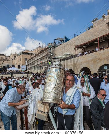 JERUSALEM, ISRAEL - OCTOBER 12, 2014: Morning autumn Sukkot. The area in front of Western Wall of  Temple. Crowd of Jewish worshipers in white wearing prayer shawls. Sefer Torah in magnificent case.