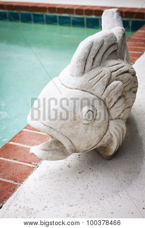 A stone fish decoration by the edge of a swimming pool.