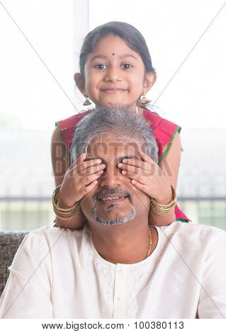 Happy Indian family at home. Asian girl giving surprise to her dad by covering dad eyes. Father and daughter indoor lifestyle.