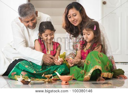 Indian family in traditional sari lighting oil lamp and celebrating Diwali, fesitval of lights at home. Little girl hands holding oil lamp indoors.
