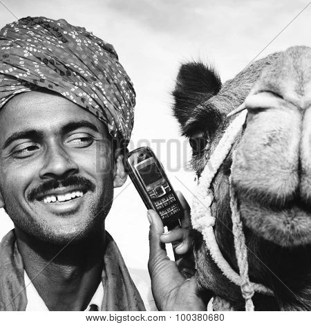 Asian Man and Camel in the Desert with Communications Concept