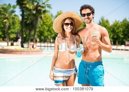 Portrait of a beautiful young couple enjoying a cocktail in front of a pool