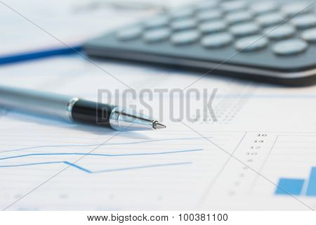 Calculator, pen and financial documents on a desk