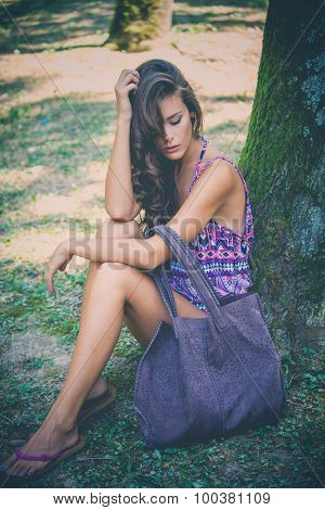 young beautiful woman sit by tree in park wearing purple print top and big leather bag, full body shot
